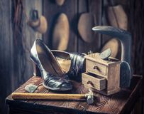 Old cobbler workshop with shoes, hammer and nails. On wooden table stock images