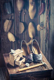 Old cobbler workshop with shoes, laces and tools. On old wooden table Stock Image