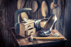 Old cobbler workshop with tools, leather and shoes Royalty Free Stock Photo