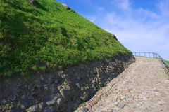 Old cobblestone road going uphill in Vilnius, Lithuania. Royalty Free Stock Photo