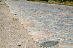 Old cobblestone road paved with stones Royalty Free Stock Image