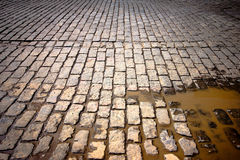 Old cobblestone street. In disrepair with muddy puddle royalty free stock photo