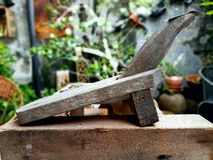 The old coconut grater. Old coconut grater on old wood in garden Royalty Free Stock Image