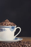 Old coffee cup filled with coffee beans Royalty Free Stock Images