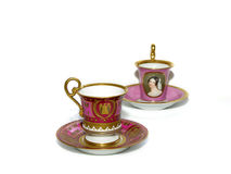 Old coffee cups and saucers. Antique coffee cups and saucers decorated in gold, pink and portraits Royalty Free Stock Images
