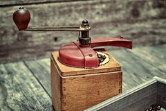 Old coffee grinder. Old coffee grinder and coffee beans on a wooden background Royalty Free Stock Photos