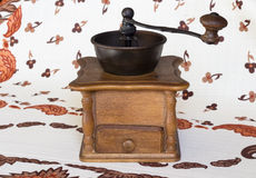 Old coffee grinder (coffee mill) brown in color.  on tablecloth Royalty Free Stock Photos