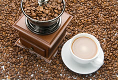 Old coffee grinder and a cup of coffee Stock Photo