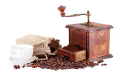 Old coffee grinder and cup of coffee. Stock Photos