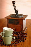 Old coffee grinder and cups. Details of an old, manual coffee grinder with coffee beans and coffee cups in the foreground Stock Photos
