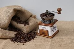 Old coffee grinder with filled coffee beans next to a coffee sack royalty free stock photos