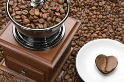 Old coffee grinder and heart on a saucer Stock Image