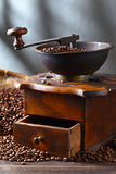 Old coffee grinder and roasted coffee beans on wooden table Stock Images