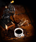 Old_coffee_mill _with_cup_of_coffee_on_tile_table. Old coffee mill with cup off coffee on tile table Royalty Free Stock Images