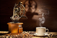 Old coffee mill and cup on wooden background Stock Photo