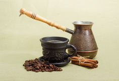 Old coffee pot, black cup with coffee, cinnamon, coffee beans Stock Images