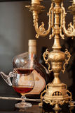 Old cognac and candle. Old cognac standing on a table with wine glasses and an antique chandelier Stock Photo