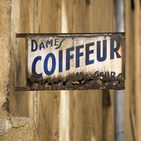 Old Coiffeur Sign in France. Old, rusting coiffeur sign in the Old Town area of Lyon, France Stock Photo