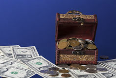 Old coins in chest with dollar bills on blue background with reflections Stock Photography