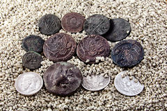 Old coins on white sand Royalty Free Stock Photo