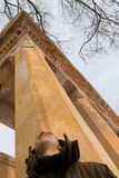 Old colomn. The young man looks upwards at an old column Stock Photography