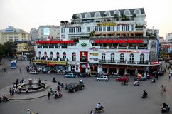 Old colonial building and roundabout with fast food restaurants Hanoi`s Old Quarter Vietnam. Hanoi, Vietnam - March 20, 2018: A view of a main roundabout with a Royalty Free Stock Photo