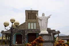 Old colonial catholic church and white Jesus Christ statue. Lang Co, Vietnam - September, 2015: Old colonial catholic church near a beach and white Jesus Christ royalty free stock photo