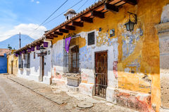 Old colonial houses & volcano, Antigua, Guatemala. Antigua, Guatemala - April 13, 2017: Old colonial houses with purple Lent banners hanging in the windows & royalty free stock image