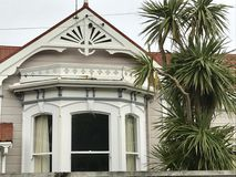 Old colonial style house detail, Petone Wellington New Zealand. Decorative architecture with bay windows, weatherboard house and cabbage tree garden foliage in royalty free stock photography