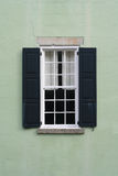 Old colonial window with shutters. Old colonial window with black shutters and handmade hardware Stock Images