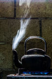 Old color black kettle. The old color black aluminium kettle boiling water on the gas stove Stock Image