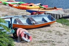 Old colored boats and lifebuoys in the sand on the beach stock images