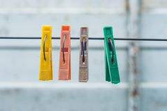 Old colored clothespins hanging on a wire for drying clothes. stock photo