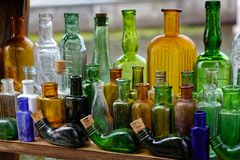 Old colored empty glass bottles are scarce stock photos