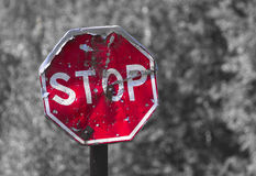 Old colored traffic sign STOP. Small depth of sharpness. Black and white blured background Royalty Free Stock Image