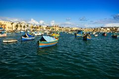 Boats Luzzu at Marsaxlokk harbor. Old Colorful Boats Luzzu in Marsaxlokk harbor at sunny day. Blue sky with clouds royalty free stock photo