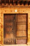 Old colorful carved wooden door with forged details in Spain. Old colorful carved wooden door with forged details in a small village in Castilla La Mancha Stock Photo