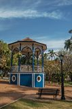 Old colorful gazebo and lighting pole in the middle of verdant garden full of trees, in a sunny day at São Manuel. royalty free stock images