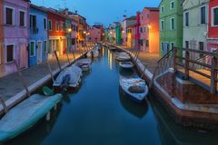 Old colorful houses and boats at night in Burano Stock Photo