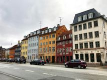 Old colorful houses in the street of the old part of Copenhagen along the gray paved road royalty free stock photo