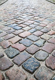 Old colorful shining cobblestone road Stock Photos