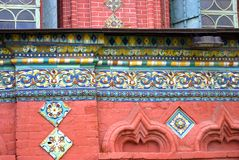 Old colorful tail on the red bricks wall of Epiphany church. Royalty Free Stock Photo