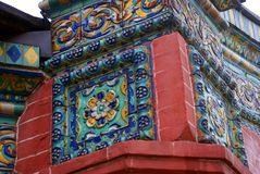 Old colorful tail on the red bricks wall of Epiphany church. Stock Photos