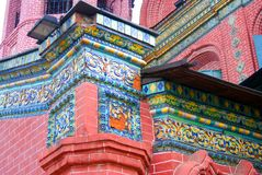 Old colorful tail on the red bricks wall of Epiphany church. Royalty Free Stock Images