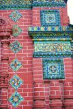 Old colorful tails on the red bricks wall of Epiphany church. Stock Photos