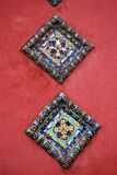 Old colorful tiles on the red bricks wall of Epiphany church. Royalty Free Stock Images