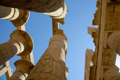 Old columns praise to high heaven. Ancient ruined columns of Karnak (Egypt) against blue sky background. All people made objects tumble into ruins but sky Royalty Free Stock Images