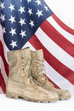 Old combat boots with American flag. In the background Stock Photography