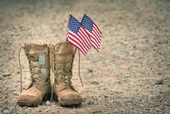 Old combat boots with dog tags and American flags. Old military combat boots with dog tags and two small American flags. Rocky gravel background with copy space Stock Image
