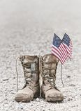 Old combat boots with dog tags and American flags. Old military combat boots with dog tags and two small American flags. Rocky gravel background with copy space stock photos